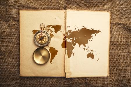 navigate: Vintage open book with old navigation compassand world map.