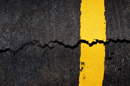 yellow line: Yellow line on cracked asphalt road, urban texture