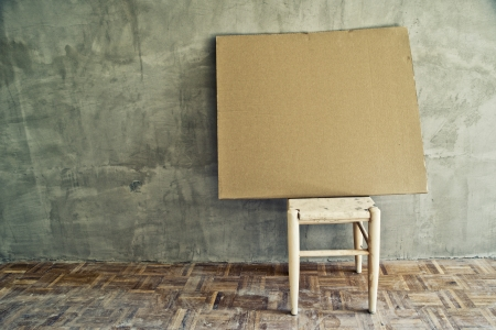 antique furniture: Old vintage chair and empty cardboard in grungy interior. Loneliness, estrangement, alienation concept.