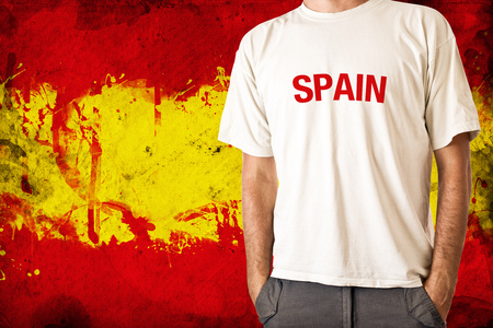 Man in white shirt with title SPAIN, Spanish flag in background photo