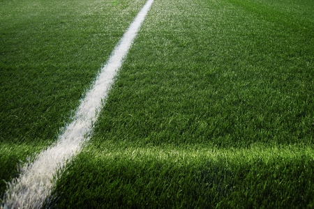grassy field: Artificial turf at soccer field, green plastic grass as background