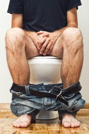 pantalones abajo: Hombre sentado en el inodoro con los pantalones abajo.