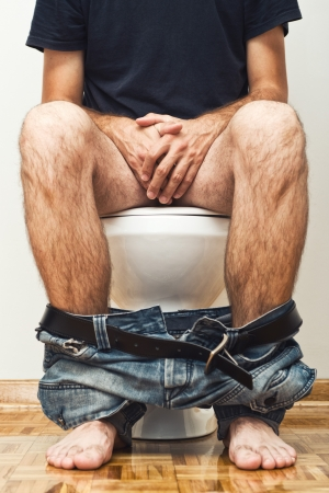 defecate: Man sitting on toilet with his pants down. Stock Photo