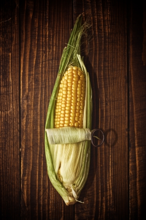 can opener: Ear of corn opening with can opener on wooden background. Autumn harvesting season.