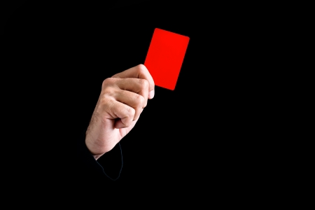 arbitrator: Soccer referee giving red card on black background.