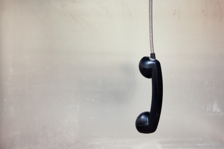 Hanging vintage phone receiver over a grunge background photo