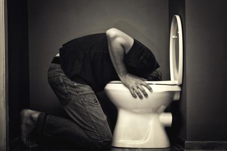 borracho: Hombre vómitos en el inodoro Foto de archivo
