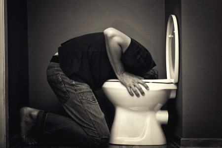Man vomiting in toilet bowl