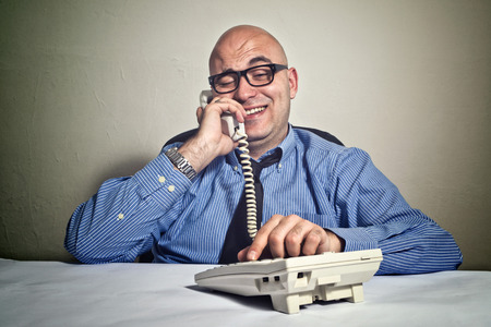 swindler: Smiling businessman at office desk with telephone. Wheeler dealer or business crook. Stock Photo