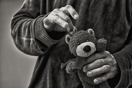 maltrato infantil: Hombre whacking oso de peluche, el concepto abuso infantil
