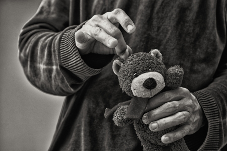 Man whacking teddy bear, child abuse concept