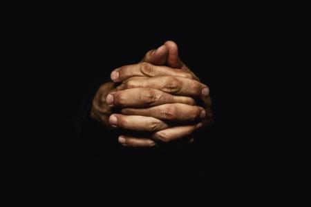 Mannelijke handen gekruist voor het gebed in het donker