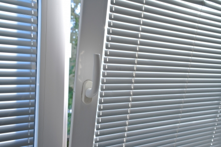 a blind: Venetian blinds on window, close up image focusing on window handle.
