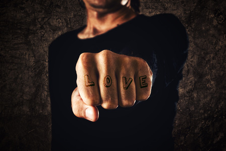 clenched: Love tattoo. Hand with clenched fist on dark background. Power, determination, resistance concept. Stock Photo