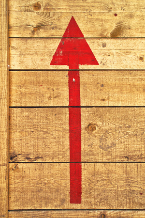 direction of the arrow: red direction arrow on wooden background Stock Photo