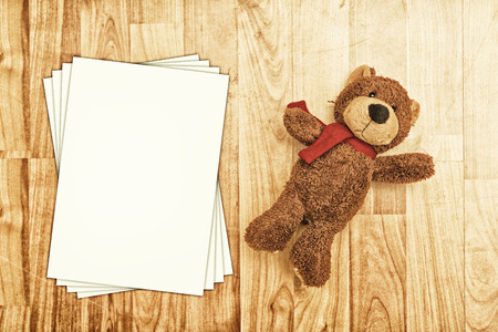 stuffed toy: Bear toy on laminated wooden floor with empty papers