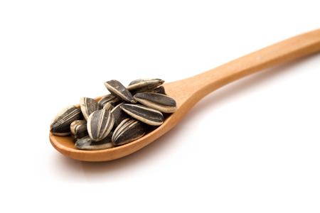 Sunflower seeds on wood spoon. Image is taken over white background.