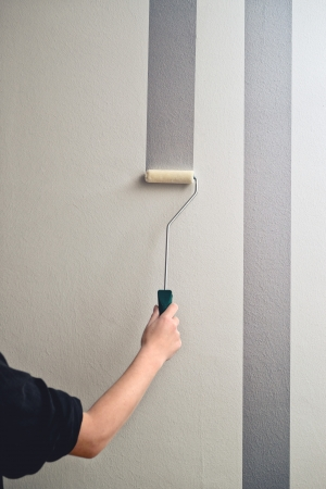 Man painting an interior wall of the room with paint roller