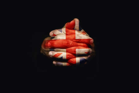 Crossed hands with United Kingdom flag painted on fingers. Prayer for UK. photo