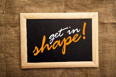 get in shape: get in shape, motivational message on black board.