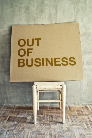 nonexistent: Out of business message on cardboard left on empty chair in obsolete room.
