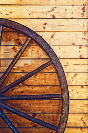 old wood farm wagon: Old horse cariage wooden wheel leaning on the wooden wall