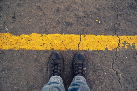 border line: Male sneakers on the asphalt road with yellow line  Border line concept, danger or warning sign