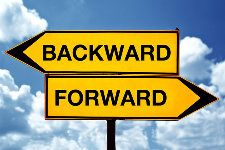 backward: Backward or forward opposite signs. Two opposite signs against blue sky background.