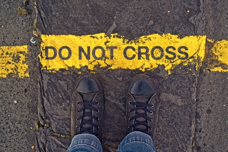 Male sneakers on the asphalt road with yellow line and title Do Not Cross. Border line concept, danger or warning sign.