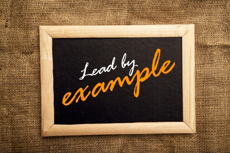 examples: Lead by example note on black message board Stock Photo