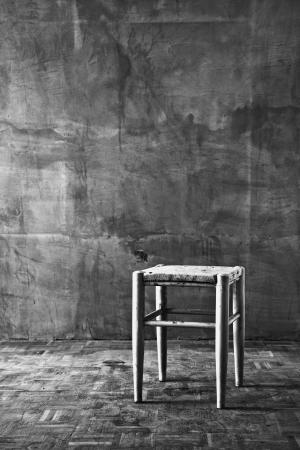 alienation: Vintage old wooden chair in grungy interior  Loneliness, estrangement, alienation concept  Stock Photo