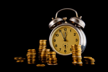 coin stack: Golden coin stack and vintage clock on dark