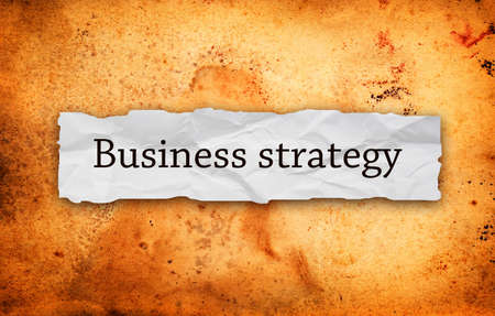 mangement: Business strategy title on piece of crumpled paper over grunge background