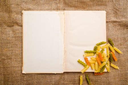 Italian fusilli or rotini and open recipe book with blank page photo