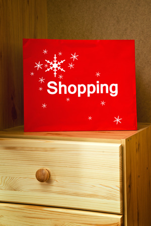 christmas shopping bag: Red Christmas Shopping bag on wooden drawer of retail store cabinet. Stock Photo
