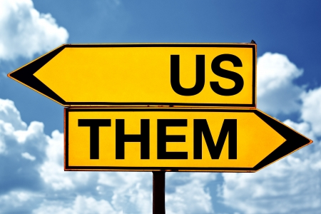 group direction: Us or them, opposite signs  Two opposite signs against blue sky background  Stock Photo