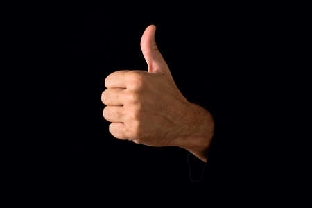 Man giving thumb up on dark black background  Stock Photo - 24435688