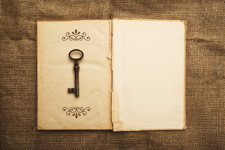 diary page: Vintage open book with old grunge paper textured pages and rusty key Stock Photo