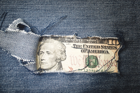 Twenty dollars bill through torn blue jeans texture. American economy concept. photo