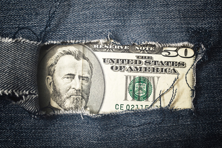 Fifty dollars bill through torn blue jeans texture. American economy concept. photo