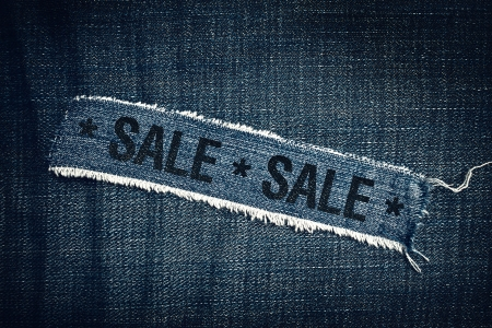 commercial event: Sale title on Torn blue jeans texture. Commercial event in retail store.
