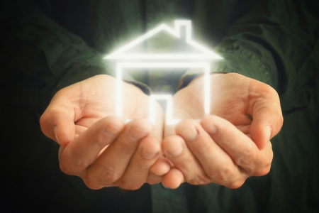 selling house: House in hands of a man  Man holding house in cupped hands  House selling or home insurance concept