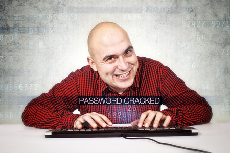 Computer hacker cracked security password. Bald smiling computer hacker typing computer keyboard. photo