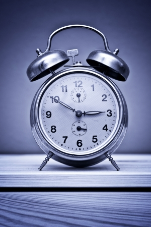vigilance: Retro vintage alarm clock on wooden table at night, insomnia concept  Stock Photo