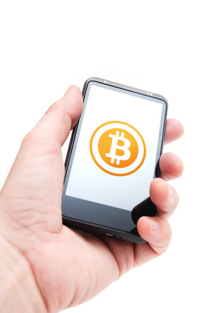 Hand holding smart phone mobile with bitcoin currency symbol photo