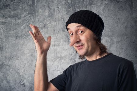 Liar with long nose, Pinocchio concept  Casual man with black cap is a big liar and deceiver  Stock Photo