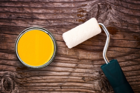 Small paint roller and color tin can on old wood background  Redecoration and renovation concept  photo