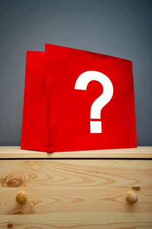 buying questions: Red shopping bag with question mark on wooden cabinet Stock Photo