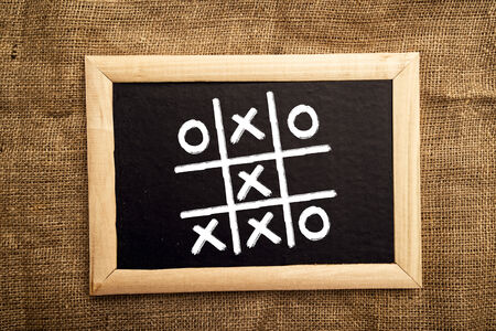 tic tac toe: Tick tack toe on black message board, abstrct of business success and achievement Stock Photo
