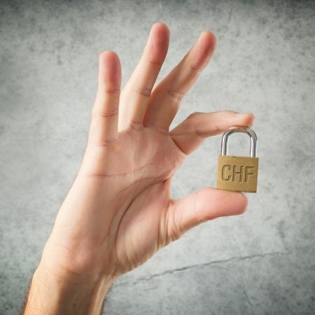 frank szwajcarski: Hand gospodarstwa kłódkę z frank szwajcarski symbol waluty. Bezpieczeństwo i pojęcie ubezpieczenia.